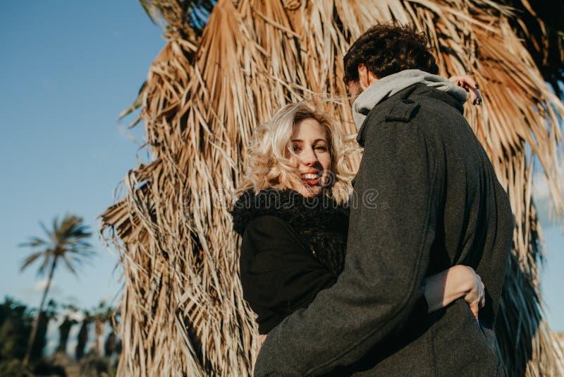 Mujer rubia que sonríe mientras que ella abraza en su novio en la puesta del sol con una palmera en el fondo imagen de archivo libre de regalías