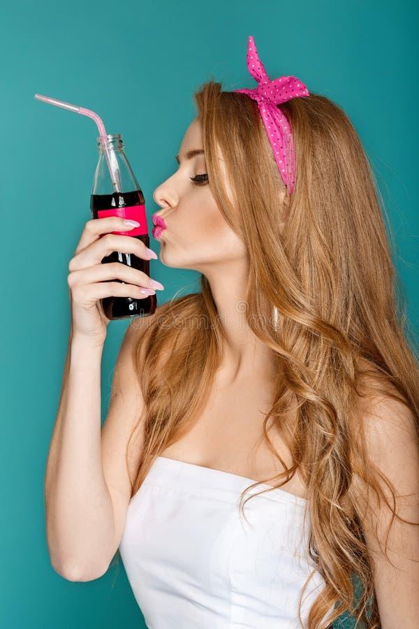Mujer rubia que sostiene la botella de cristal con soda imagen de archivo libre de regalías