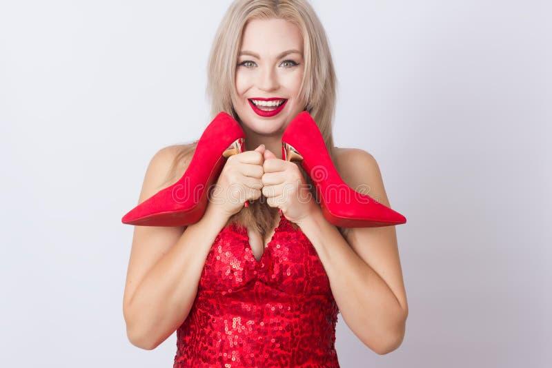 Mujer rubia que sostiene los tacones altos rojos en sus manos foto de archivo