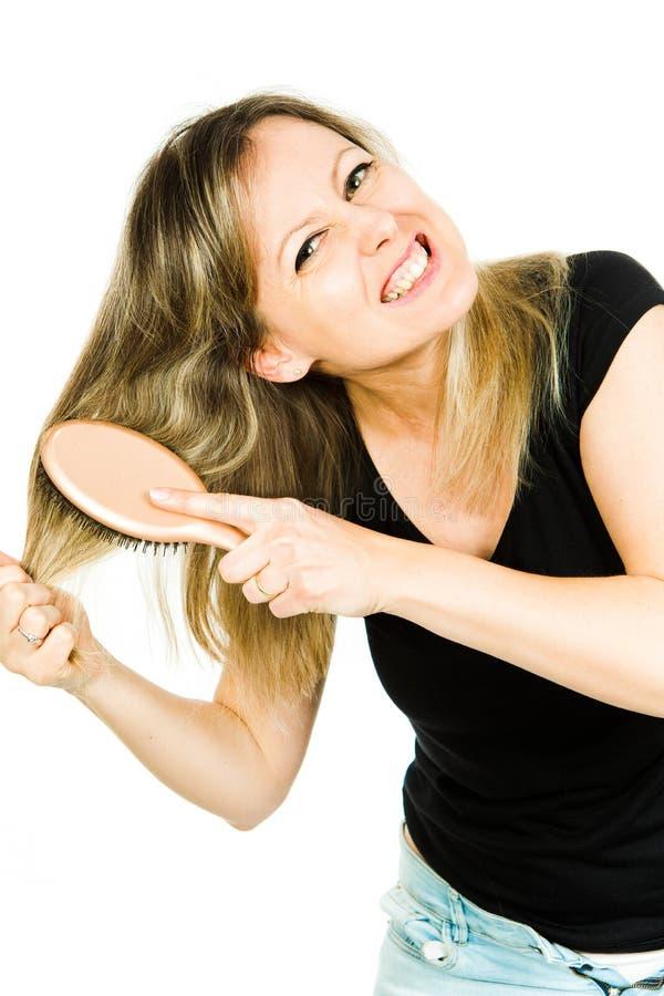 Mujer rubia que tiene problema con el cepillado del pelo enredado recto largo con el cepillo para el pelo - situación desesperada fotografía de archivo