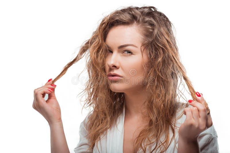 Mujer rubia que toca su pelo y que mira la cámara aislada en blanco imagen de archivo libre de regalías