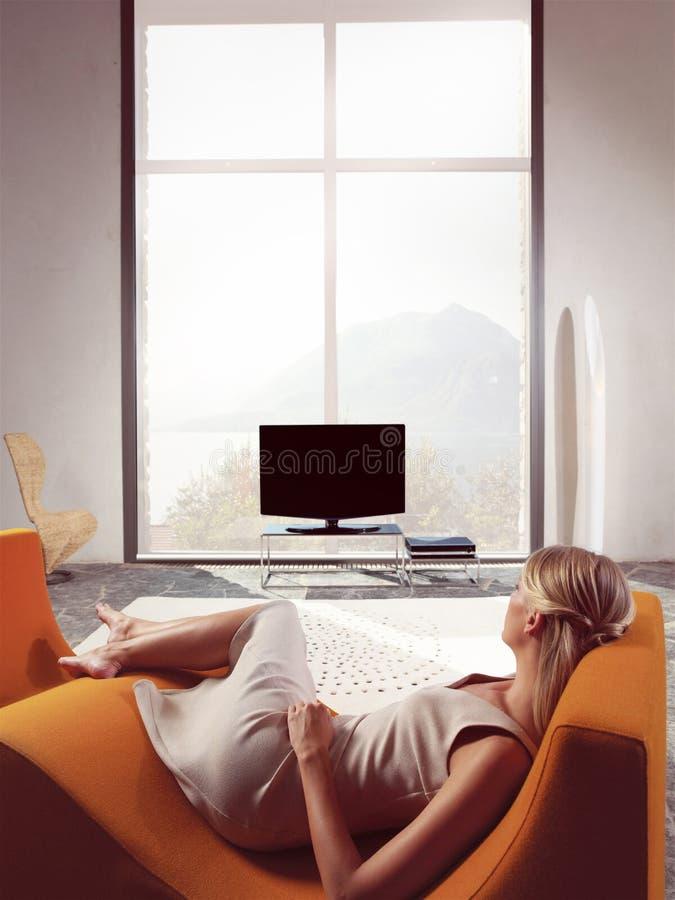 Mujer rubia que ve la TV imagen de archivo libre de regalías