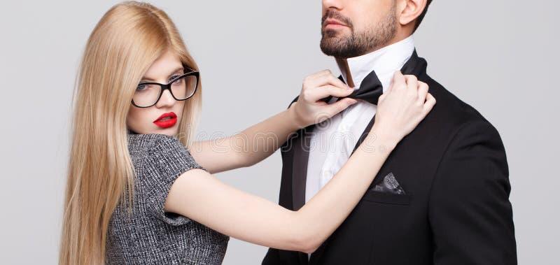 Mujer rubia sensual que ajusta el arco según hombre, deseo del lazo fotografía de archivo libre de regalías