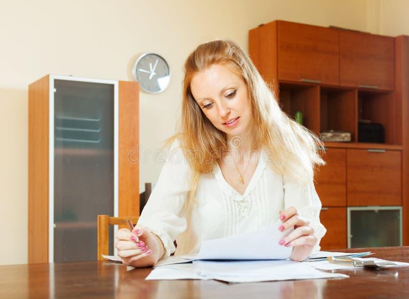 Mujer rubia seria que mira documentos financieros fotos de archivo libres de regalías