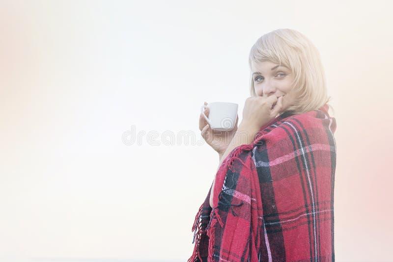 Mujer rubia sola en la playa con la taza de bebida caliente, tela escocesa roja caliente foto de archivo