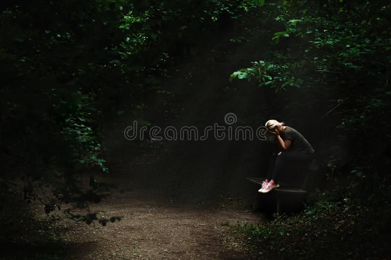 Mujer rubia sola y triste que se sienta en un banco en un punto ligero en el medio de la trayectoria de bosque oscura imágenes de archivo libres de regalías