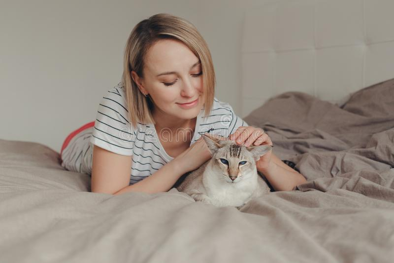 Mujer rubia sonriente caucásica que miente en cama en dormitorio en casa y que acaricia frotando ligeramente el gato punto-colore foto de archivo libre de regalías