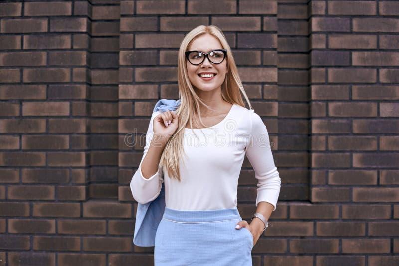 Mujer rubia sonriente en los vidrios que sostienen la chaqueta en la calle imagenes de archivo