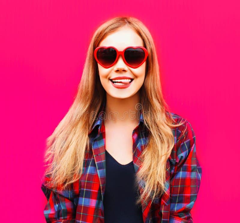 mujer rubia sonriente feliz del retrato del primer en gafas de sol rojas en forma de corazón en rosa colorido foto de archivo libre de regalías