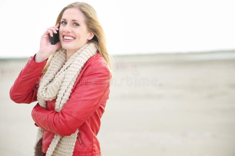 Mujer rubia sonriente hermosa que habla en el teléfono foto de archivo libre de regalías