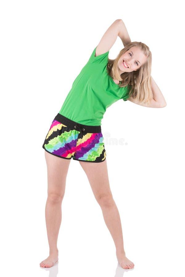 Mujer rubia sonriente que lleva en la ropa de deportes que se coloca con las piernas en el ancho de hombros que inclina al lado imágenes de archivo libres de regalías
