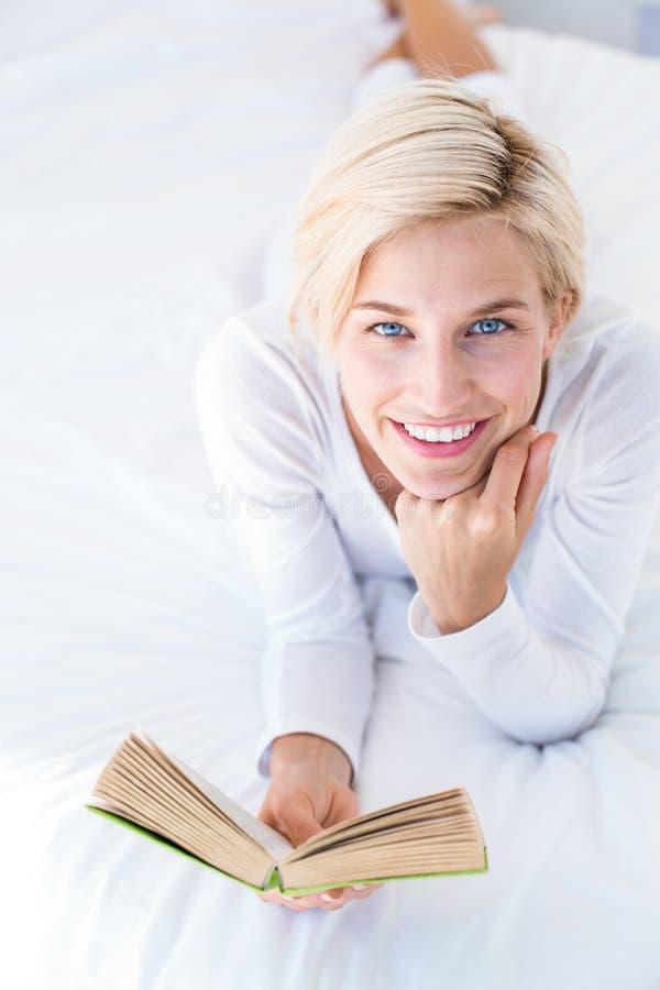 Mujer rubia sonriente que miente en la cama y la lectura de un libro fotografía de archivo