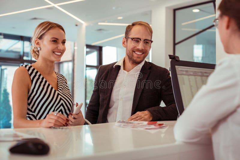 Mujer rubia sonriente que permanece con su hombre barbudo en una recepción fotografía de archivo