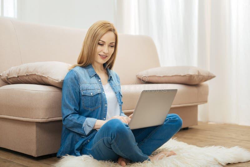 Mujer rubia sonriente que se sienta con un ordenador portátil imágenes de archivo libres de regalías