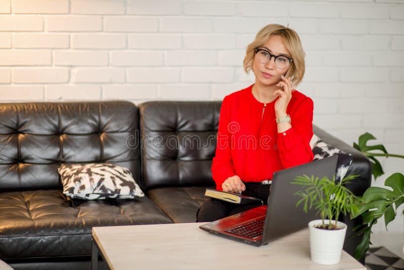 Mujer rubia sonriente que se sienta en silla de la oficina Ayudante joven en el lugar de trabajo foto de archivo libre de regalías