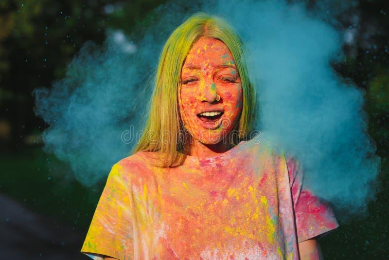 Mujer rubia sorprendida que juega con el estallido del polvo colorido seco en el festival de Holi fotografía de archivo