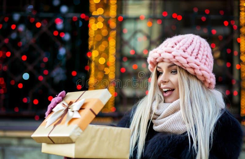 Mujer rubia sorprendida que lleva el casquillo hecho punto y la capa caliente, holdin foto de archivo