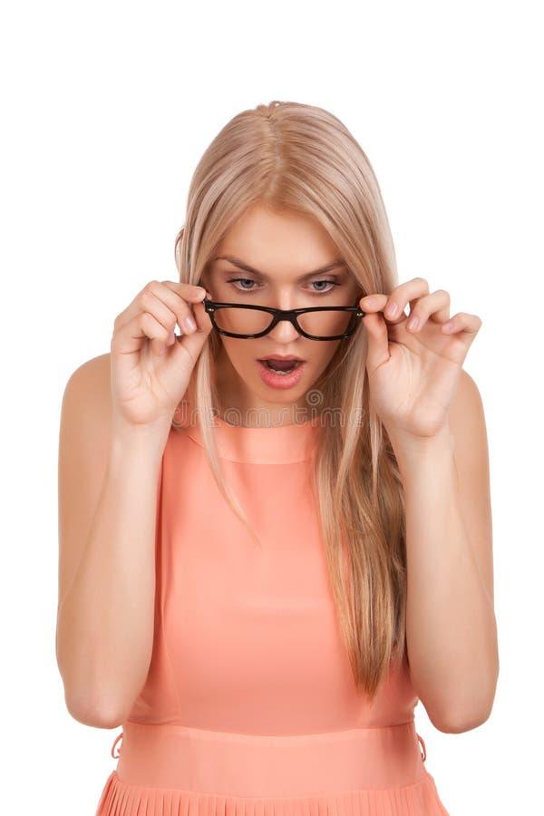 Mujer rubia sorprendida que mira abajo sobre los vidrios imagen de archivo libre de regalías