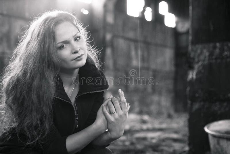 Mujer rubia triste hermosa en sigarette que fuma arruinado del edificio fotografía de archivo libre de regalías