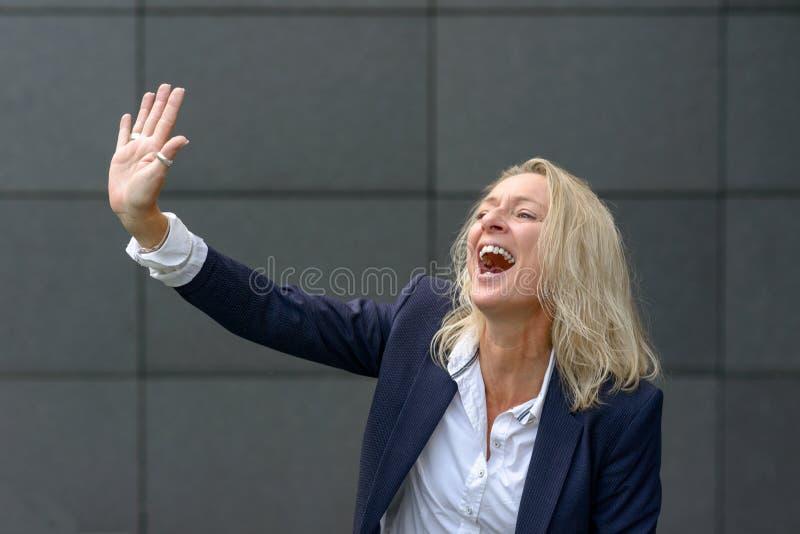 Mujer rubia vivaz que ríe agitar imagen de archivo libre de regalías