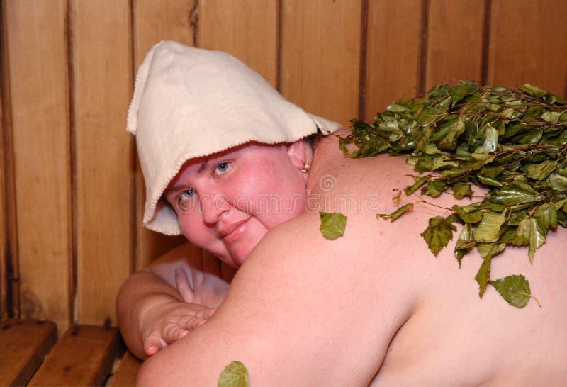 Mujer rusa en banco en casa de baños imagen de archivo