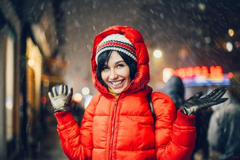Mujer salida feliz que se divierte en la calle de la ciudad de Nueva York debajo de la nieve en el sombrero y la chaqueta que lle imágenes de archivo libres de regalías