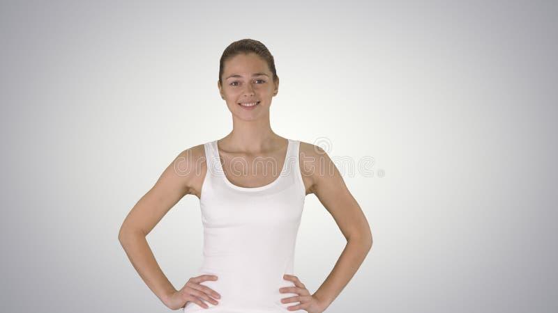 Mujer sana activa confiada satisfecha en ropa de los deportes con las manos en caderas que camina en fondo de la pendiente foto de archivo libre de regalías