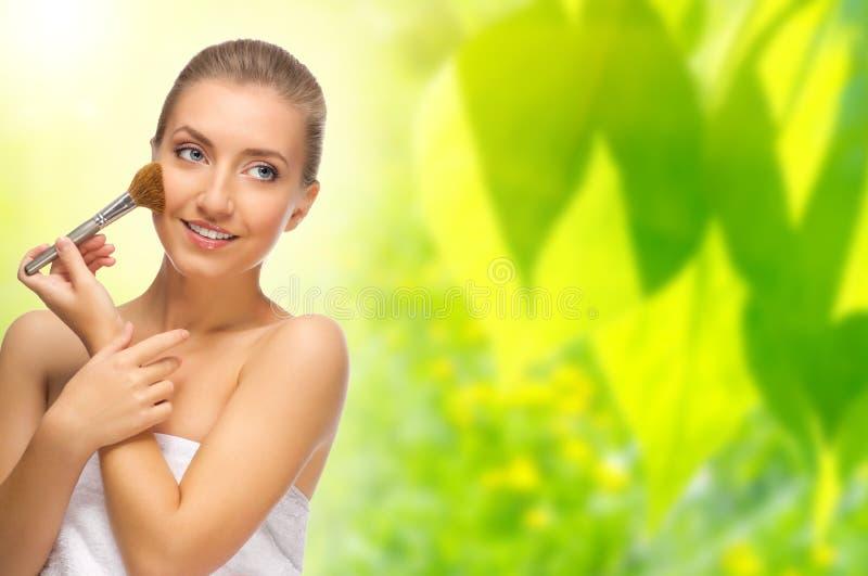 Mujer sana con el cepillo del maquillaje en fondo de la primavera fotos de archivo libres de regalías