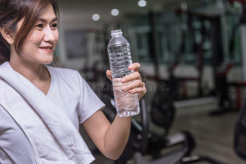 Mujer sana del deporte que mira el agua de la bebida imagen de archivo