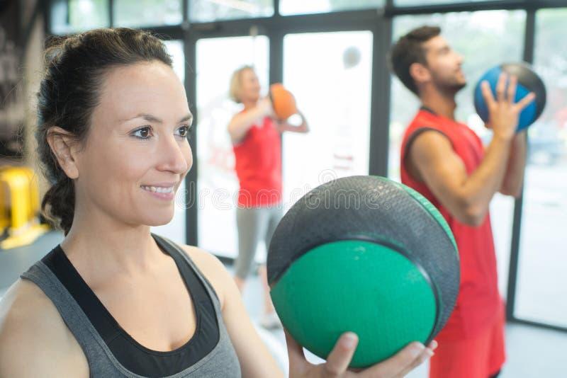 Mujer sana fuerte que sostiene la bola de medicina pesada en entrenamiento del gimnasio imágenes de archivo libres de regalías