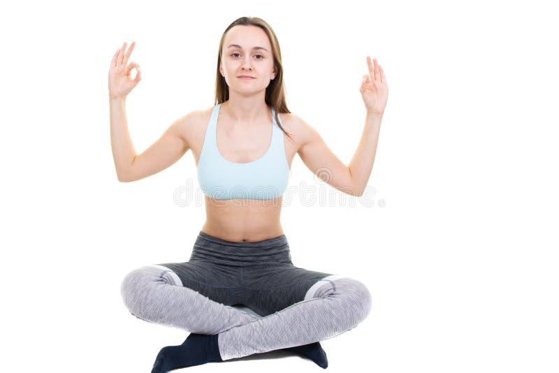 Mujer sana joven que hace los ejercicios de la yoga aislados en el fondo blanco imagenes de archivo