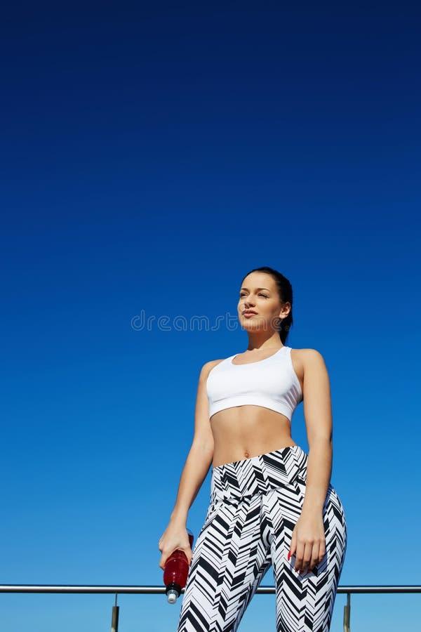 Mujer sana magnífica con la figura hermosa que disfruta de tarde soleada durante su entrenamiento diario que entrena al aire libr foto de archivo libre de regalías