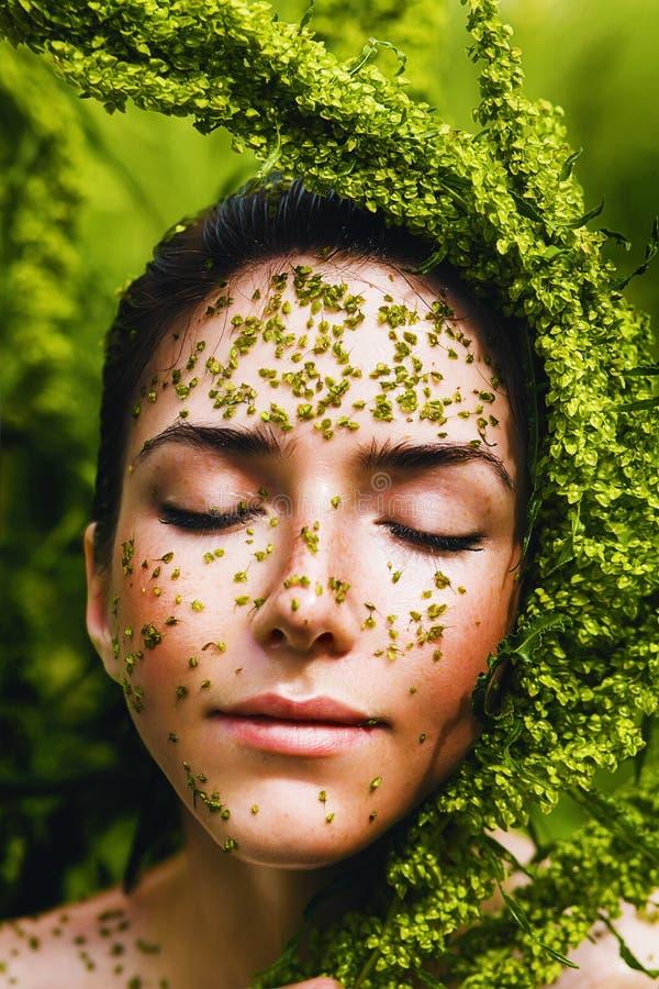 Mujer sana sensual que sostiene la planta en cara imagenes de archivo