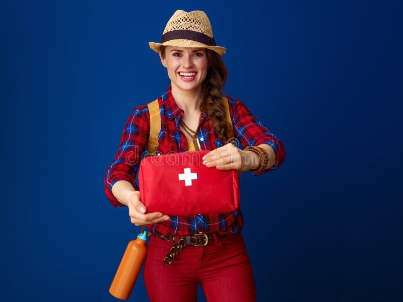 Mujer sana sonriente del viajero que muestra el equipo de primeros auxilios foto de archivo libre de regalías