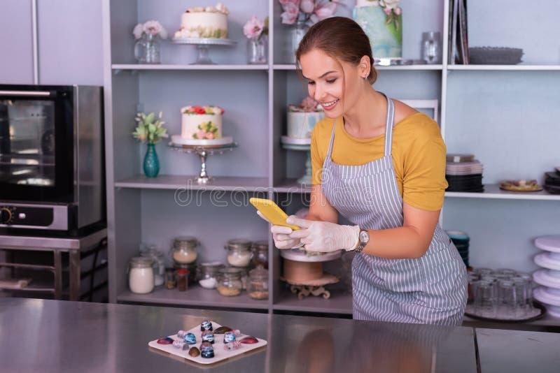 Mujer satisfecha de emisión que hace la foto de sus chocolates perfectos fotos de archivo libres de regalías