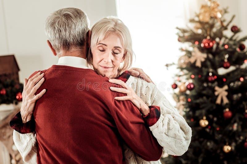 Mujer satisfecha tranquila que abraza a su marido que se cierra los ojos fotografía de archivo libre de regalías