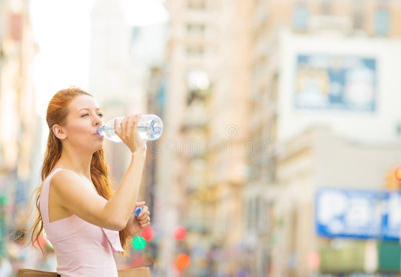 Mujer sedienta Agua potable de la mujer de la botella plástica en una ciudad el día de verano fotos de archivo