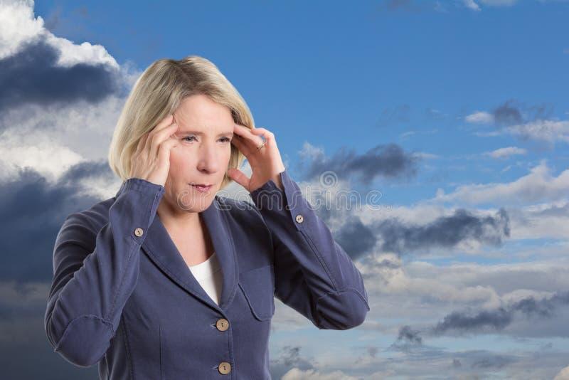 Mujer sensible del tiempo con dolor de cabeza fotos de archivo