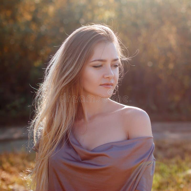 Mujer sensual atractiva que presenta en el parque en día soleado del otoño imagenes de archivo
