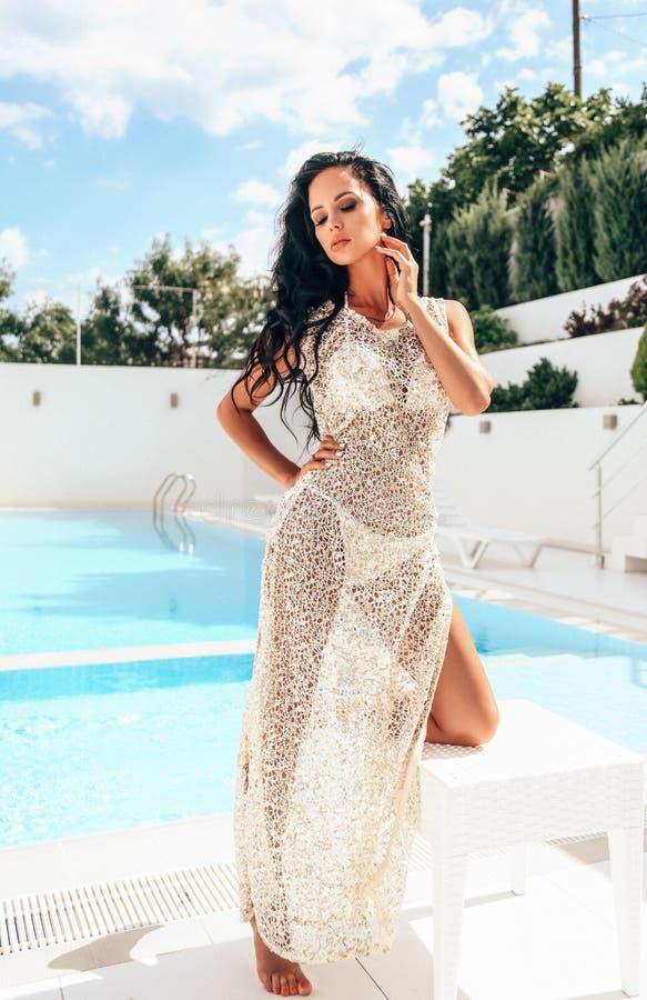 Mujer sensual con el pelo oscuro en traje que nada elegante y los accesorios que se relajan en la piscina imágenes de archivo libres de regalías
