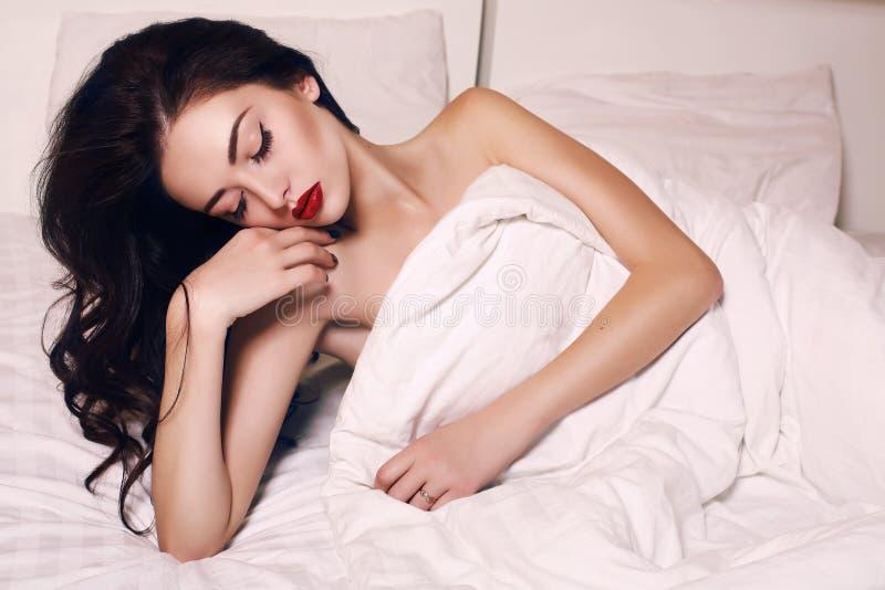 Mujer sensual con el pelo oscuro y el maquillaje brillante que mienten en cama foto de archivo