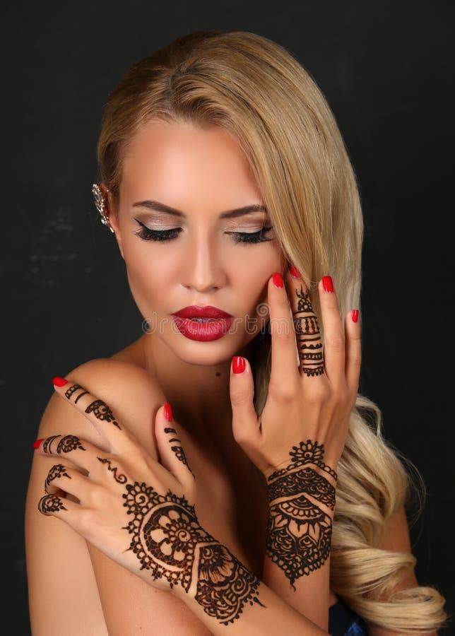 Mujer sensual con el pelo rubio con el tatuaje de la alheña en las manos imagen de archivo