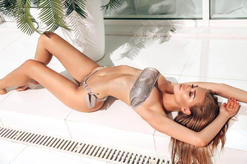 Mujer sensual con el pelo rubio en el traje que nada elegante que presenta cerca de piscina foto de archivo