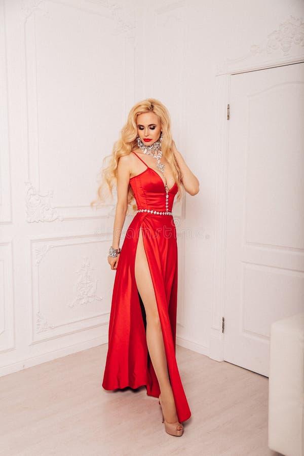 Mujer sensual con el pelo rubio largo en vestido de noche lujoso imagen de archivo