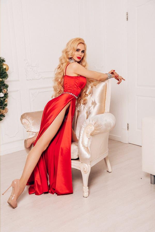Mujer sensual con el pelo rubio largo en vestido de noche lujoso fotos de archivo