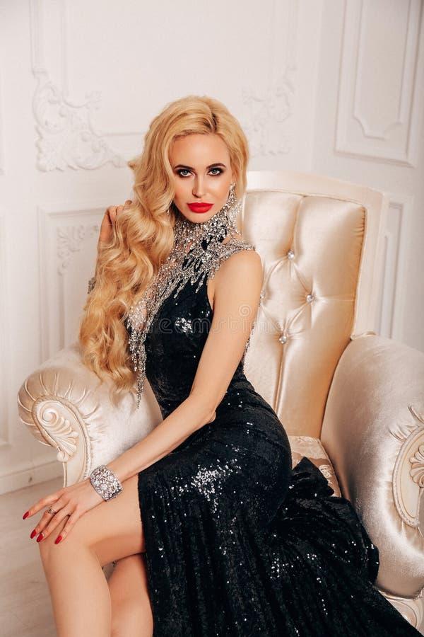 Mujer sensual con el pelo rubio largo en vestido de noche lujoso imagenes de archivo