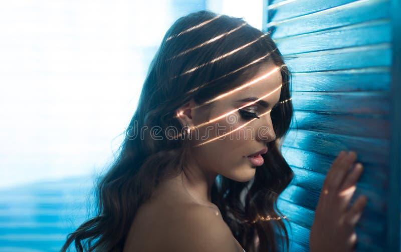 Mujer sensual con maquillaje en la ventana Hembra perfecta Mujer de la moda con maquillaje y pelo rizado Muchacha elegante con foto de archivo
