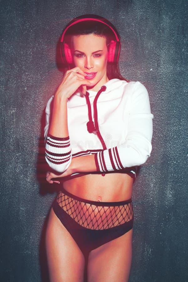 Mujer sensual de DJ con los auriculares y la luz roja que presentan en la noche foto de archivo libre de regalías