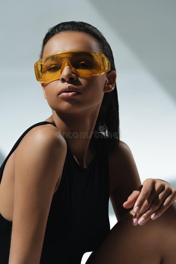 Mujer sensual elegante afroamericana que toma el sol en gafas anaranjadas protectoras fotografía de archivo libre de regalías