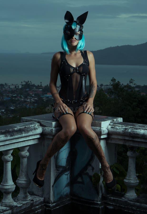 Mujer sensual en peluca azul con las correas de cuero y la máscara del conejo fotos de archivo